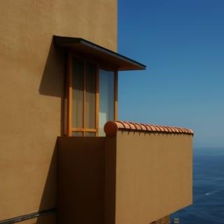 外壁は左官仕上げ。アースカラーの抑えた色調が自然豊かな風景によくなじむ