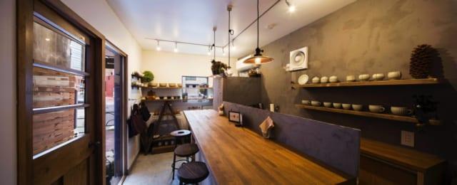 1階 店舗/奥さまが作家から買い付けたうつわが並ぶ店内。側面のガラス窓と、大通り側に設けた窓で採光と開放感を得ている。おいしい料理とホッとくつろげる雰囲気が人気で、昼どきは近隣の会社員でにぎわう