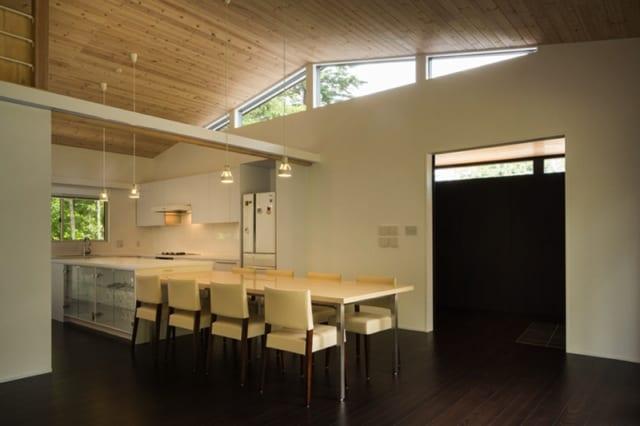 ダイニング・キッチン/ハイサイドの窓から燦々と光がそそぐ気持ちのよい空間。アイランドタイプの調理台とダイニングテーブルがひと続きになっていて、大人数の会食もゆったり楽しめる。出入口の先にはワインセラーなどを置ける食品保管スペースもある