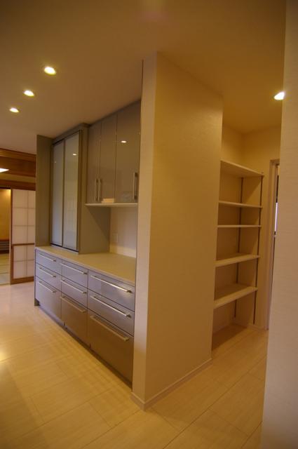 キッチンの背面収納を含め、四方から取り出せる多様な収納スペースを一か所に設置。廊下側から出入りする収納は納戸のような広いスペース。廊下を挟んだ北側にはパントリーを