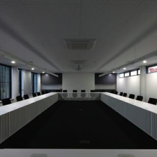 撮影:GEN INOUE  ふすま~会議室/写真左手、ブラインドの代わりにふすまが窓を覆っている。また、住宅地に接する2階東面にあるため、左手の窓から有孔折板がうかがえるが暗さは感じない