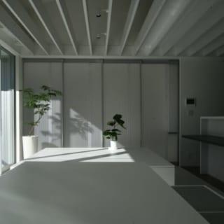 2階 リビング~ダイニング/広いリビングダイニングにはつり引き戸の仕切りを設置し、空間の使い方に多様性を持たせている。また、トップライトのあるダイニング側は天井を格子にして光を取り入れ、キッチン側の天井裏は収納スペースとして活用