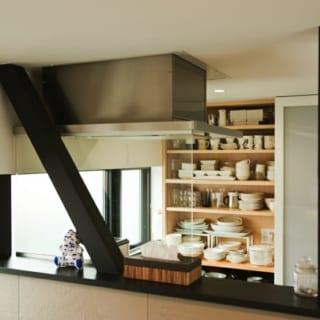 キッチンカウンター越しのシンク背面には、お気に入りの食器類がたっぷりしまえる造り付けの収納棚を。向かって左側に食器、右側には電子レンジなどの家電を収納。収納棚の裏側はパントリーに