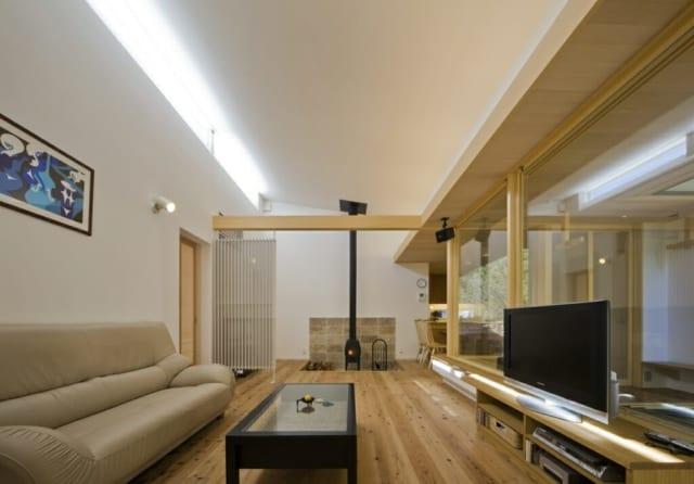 【写真】リビングに薪ストーブがあるだけで、くつろぎ感が格段にアップ。右手の庭の一部に土間を打ち、薪割りスペースも設置。床は杉板、壁や天井はすべて漆喰で仕上げ、自然素材に囲まれた心地よい空間をつくっている。