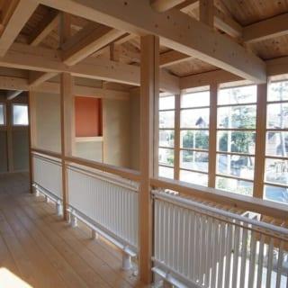 T邸、サンルーム/格子のガラス窓から明るい陽射しが注ぎ込む2階のフリースペース