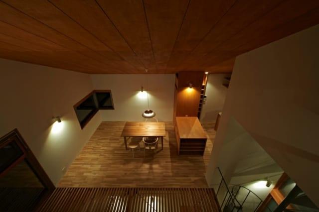 屋外のバルコニーから見た室内/高さを揃えた家具と間接照明が大人っぽい雰囲気を醸し出している