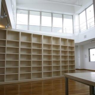 6階自宅 本棚/図書館のように大きな本棚は斜めに設置。天井の高い大空間なので、大きな家具を造り付けてもまったく圧迫感がない