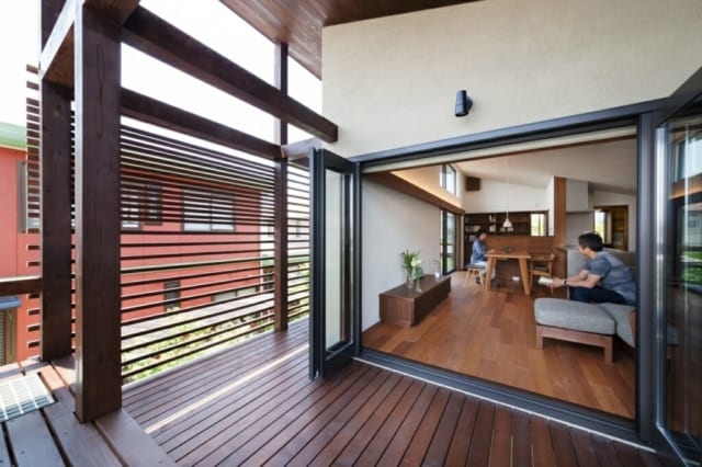 LDKと一体感をなす回遊デッキテラス。南側の木製ルーバー上部は隣家からの視界をより遮るため間隔を狭めた。