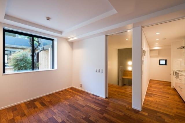 賃貸住戸 居室~キッチン/メゾネットタイプの住戸。写真右は料理が楽しみになりそうな、ゆったりとしたキッチン。写真中央のコンクリート打ち放し部分は階段で、下りると居室、バスルームといったプライベート空間がある