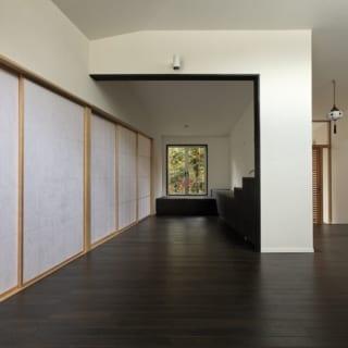 ゲストスペース 広間(フローリング)/来客用の広間はフローリングスペースと畳スペースがあり、障子で仕切ることができる。重厚感のあるフローリングスペースは、Kさんの奥さまの趣味であるグランドピアノを悠々置ける広さをとった。内装は親世帯がダークブラウン、子世帯が白を基調としているのに対し、ゲストスペースは限りなく黒に近い濃茶でまとめている