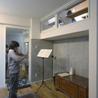 音楽室でバイオリンを練習中。鏡を置いて、フォームチェックをすることもできる。右上の窓の向こうはLDK
