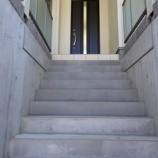 玄関へのアプローチ。玄関ドアは白と黒のコントラストが気に入って選んだ。中央のガラス部分で、縦に一筋、光のラインが入っているように見せる演出も。