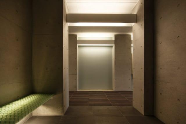 共用スペース 通路&エレベーター前/天井と床を照らす間接照明はカバーで覆われ、空間はすっきり。写真奥の曇りガラスの先は駐輪スペース。通路の光が曇りガラスを通して届くので、駐輪スペースは照明を設置しなくても十分明るい