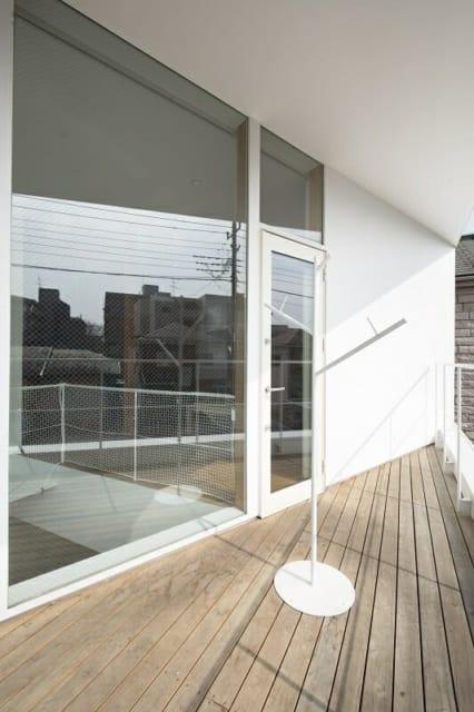 2階バルコニー/バルコニーに面した窓を可能な限り大きくとり、室内に光をたっぷり採りこめるようにした。かわいらしい木のような物干し竿スタンドのデザインも杉山さんによるもの。「懇意にしている鉄骨屋さんにお願いし、作ってもらいました」とのこと