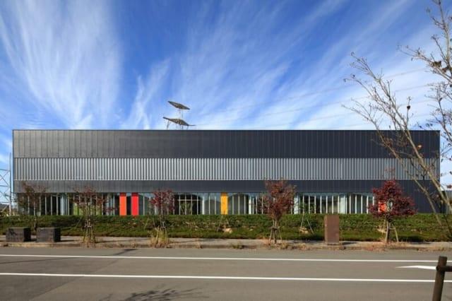 撮影:GEN INOUE  東面/住宅地から望む景色。日本、ドイツそれぞれの国旗の色とコーポレートカラーがアクセントになっている。2階窓部分の有孔折板も、壁の圧迫感を軽減している