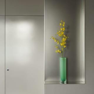 飾り棚/キッチンの出入口の向きを変える際に必要だった壁の改修にともない、ここにもビーズブラスト加工のステンレスを採用。光が白く浮き上がるように曖昧に反射し、壁の圧迫感をぐっと軽減