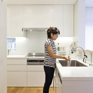 1階キッチン/オーダーでつくったキッチンは、清潔感のある白で統一。作業台の高さは奥さまの身長に合わせている。壁のタイルは透明感のあるガラスタイル