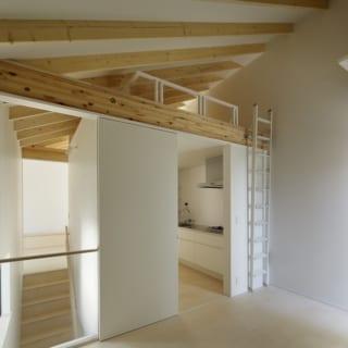 繁田諭   【写真11】A棟 2階 多目的室~キッチン・ロフト/写真左の階段をのぼった先にあるリビングダイニングと多目的に使える洋間をつないでいる。上部にはロフトを設けスペースを最大限に活用