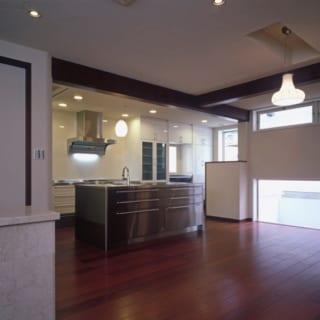 1階キッチン/ダイニングと対面するアイランドタイプ。キッチンにいる際も玄関やリビングの様子がわかりやすい。奥の白い壁で囲われた部分には、奥さまがパソコンなどを使うときのためのワークスペースもつくった