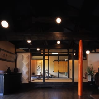 リビング/「10年経っても20年経っても変わらない空間を」というコンセプトでデザイン。全体的にダークな色使いだが、柱の1本を明るいオレンジ色にしたおかげで重苦しさがない。このセカンドハウスは親族が集まって法事などを行う場としても使われており、奥には仏壇を設えた和室もある