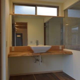 洗面所/木の床に白い洗面台が配された洗面所。シンプルにすることでスペースを広く見せ、木の風合いを生かしたつくりとなっている