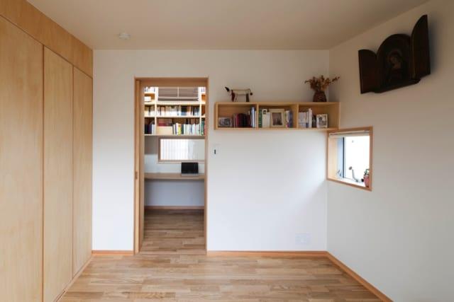 2階寝室/書斎とつながるMさんの寝室。扉を開けると書斎の室内窓からリビングの窓まで見通せて、空間の広がりを感じられる。寝具用の押入れや衣類のクロゼットなど、収納も十分に設けた