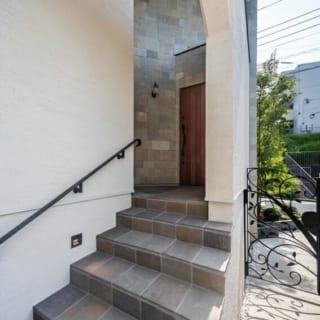 1メートルほどの高さがある玄関へと段差の緩い階段でつないでいる