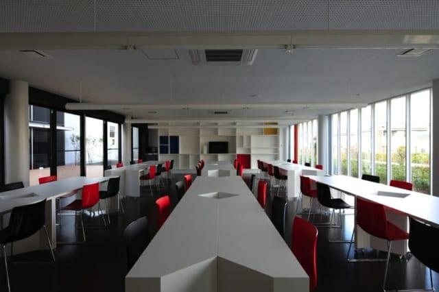 撮影:GEN INOUE  食堂/モンドリアン風の奥の棚が目を引く、カフェのような食堂。合わせてテーブルもデザイン。移動可能で、合わせると5角形にもできるよう角を削ってある。ライトはありふれた直管蛍光灯をつなげてつりさげたもの。工夫により素敵なデザインに仕上がっている