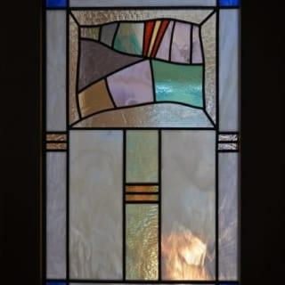 ステンドグラス/洗面室の奥にはめられたステンドグラスは、建て主さんが気に入って用意したもの。お子さんが描いていた絵がモチーフになっている。ここから柔らかい光が洗面室に注ぎ込む