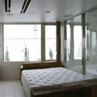 6階自宅 ベッドスペース/本棚の背後はベッドスペース。内装にはタイルや古材が用いられ、洗練されながらも温かみのある空間だ