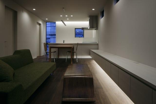 2階 夜のLDK/天井埋め込みのダウンライトのほか、キッチン背後やテレビ台の下には間接照明を設置。夜は柔らかな光でゆったりとくつろげる。ダイニングは、手もとを明るく照らすペンダントライトを採用(写真では消灯)。照明を吊るす部分のコードが見えないすっきりしたデザインを選んだ