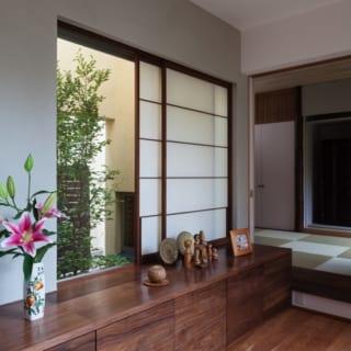 """1階廊下/和室に向かって右側には中庭、左側には小ぶりな坪庭を設えた。廊下の先には和室のみのため、和室を""""離れ""""のような感覚で使うことができる"""
