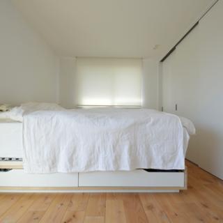 1階 寝室/1階南に位置する主寝室。写真奥が西で右側には収納棚がしつらえられている。白と木の風合いでゆったりとした清潔感あふれる空間だ