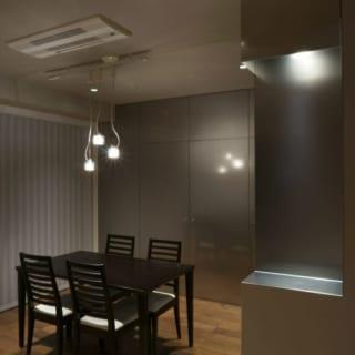 ダイニング 夜/ビーズブラスト加工のステンレスは、夜になると反射光が和らいで落ち着いた雰囲気に。素材選びが功を奏し、収納の扉も洗練されたインテリアとしての存在感を放つ