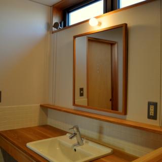 洗面所/こちらも木の風合いを生かした造りになっている。鏡の縁は、奥様と一緒に額縁の専門店で購入したもの