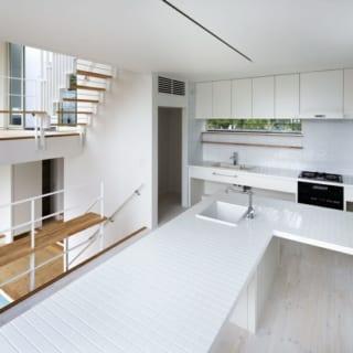 1.5階キッチン/ほかのスペースの床はパインのむく材だが、キッチンは水はね、油はねに備えて床材を水性ペンキで塗装。ダイニングテーブル代わりにもなる大きな調理台は、あえてタイル貼りとした。「目地の汚れを気にするお客さまもいらっしゃるので、試しに使ってみました。普通に掃除すれば汚れは気になりませんよ」と桜本さん