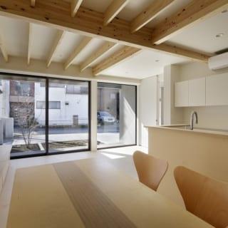 繁田諭   【写真13】B棟 1階 リビングダイニングキッチン/道路との間に庭のあるB棟は1階にリビングダイニングを配置。大きな窓で庭とのつながりを持たせ、開かれた空間に