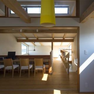 3階 通路兼多目的スペース/子ども部屋の前にカウンターを設置。この下がダイニングなので、勉強するお子さんの様子が階下でもわかりやすい。ここの天井は建物最上部となるため、採光と熱気抜きとして内倒しのハイサイドライトを設置。写真右奥の多目的なロフトまでは手すりを兼ねた本棚を造り付け。ロフトには大型窓が2箇所あり、日差しが階下までふんだんに入る