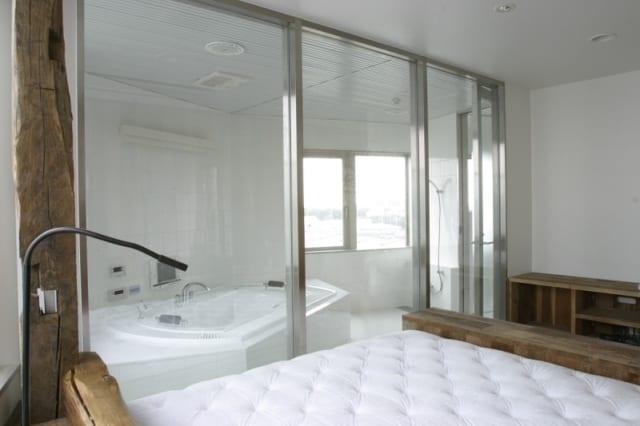 6階自宅 バスルーム/ベッドスペースとガラスで仕切られたバスルームは贅沢な広さで、眺めのよい窓もある。窓を大きくとっても人目が気にならないのは最上階の嬉しいポイント