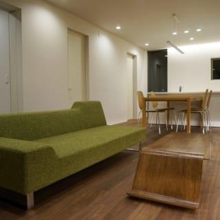 2階 LDK/リビングの家具は松岡さんが一緒に選んだ。大きなソファは「昼寝にぴったり」とSさん。リビングテーブルはウォルナットの床と同じ色調に塗装した。ソファの後ろには和室があり、写真は和室の障子を開けて壁の中に引き込んだ状態。見えるところに障子が残らず、和室とリビングの一体感が増す(※)