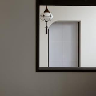 ゲストスペース 広間(フローリング)窓/広間のフローリング部分と共用表玄関ホールを仕切る壁には小さな窓があり、人の出入りがわかりやすい。以前の家で使用していたレトロな照明がちらりと見える遊び心も楽しい