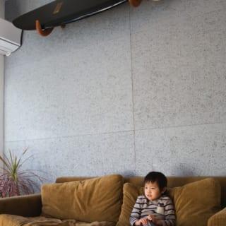 ソファーの後ろには外壁にも使われる素材であるグレーの壁材を使用。天井近くに設置した、特注のサーフボードスタンドとお気に入りのサーフボードがアクセントとなっている