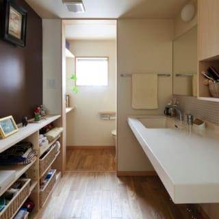 2階洗面室・トイレ/階段を上りきると左に書斎、右にお母さまの部屋と水まわり。夜遅くまで仕事をしても、1階に下りずに洗面などを行える。壁は一面だけ茶系で塗装。玄関の扉同様ヨーロッパテイストのこの色は、フランス暮らしが長かったMさんの好みに合わせている