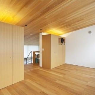 2階子ども部屋/階段を昇りきった先にある将来の子ども部屋。北向きで1年中柔らかい光が入る。間仕切りをつければ2つの部屋として使用可能。現在は家族4人の寝室として使っている