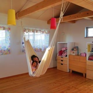 3階 子ども室/2階吹抜け側に開放されてリビングなどとゆるやかにつながる。入り口は4枚引き戸を設置でき、個室が必要になれば中央の梁で間仕切りが可能。現在はハンモックをつるして楽しい遊び場に。部屋は北西奥に位置するが、全方位に窓があり採光・通風を得られる