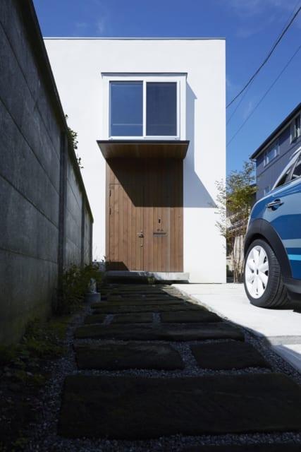玄関とアプローチ。扉はピーラー材で製作。手前の敷石は、中庭同様に鎌倉石を使用。玄関上の和室の出窓からは朝日が入る。