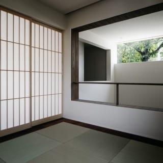 2階 和室/リビング隣接の和室は、1階の土間の吹抜けに面している。吹抜け側は断熱性のある和紙ブラインドで、すべて開けると土間のハイサイド窓を通して隣の実家の桜が見える。ブラインドとリビング側の障子を閉めれば完全な個室になり、客間として使用できる