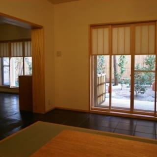 部屋から眺める庭は、外の空気や季節を感じさせてくれる、この家の大事な構成要素。上部のビル部分は障子で隠れているので、興をそがれずに済む