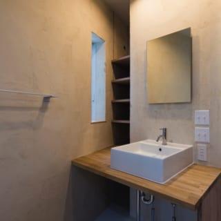 2階 洗面/トイレやバスルームと同じスペースに設けられた洗面台。横には光をとり込む縦長の窓を設置している。洗濯機置き場は水まわりスペースの外につくったおかげで、洗面やトイレはゆとりあるスペースになった