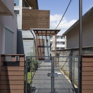 1階 アプローチ~玄関/木材とガルバリウム鋼板のバランスが絶妙な洗練された外観は、デザインの細部までこだわった。玄関庇は強化ガラス。「3階建ての高い建物で外壁に入るラインを縦にすると高さが強調されるため、横ラインとしています」と近江さん。この玄関までのアプローチには、グリーン好きの奥さまが花や野菜を育てる植栽スペースもある